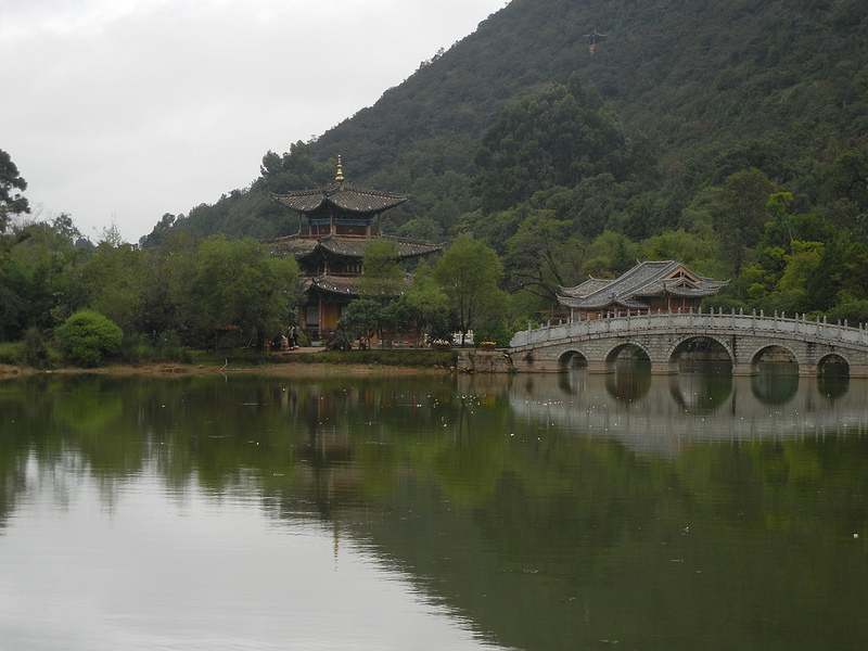 The Black Dragon Pool linked by a bridge to a historic building